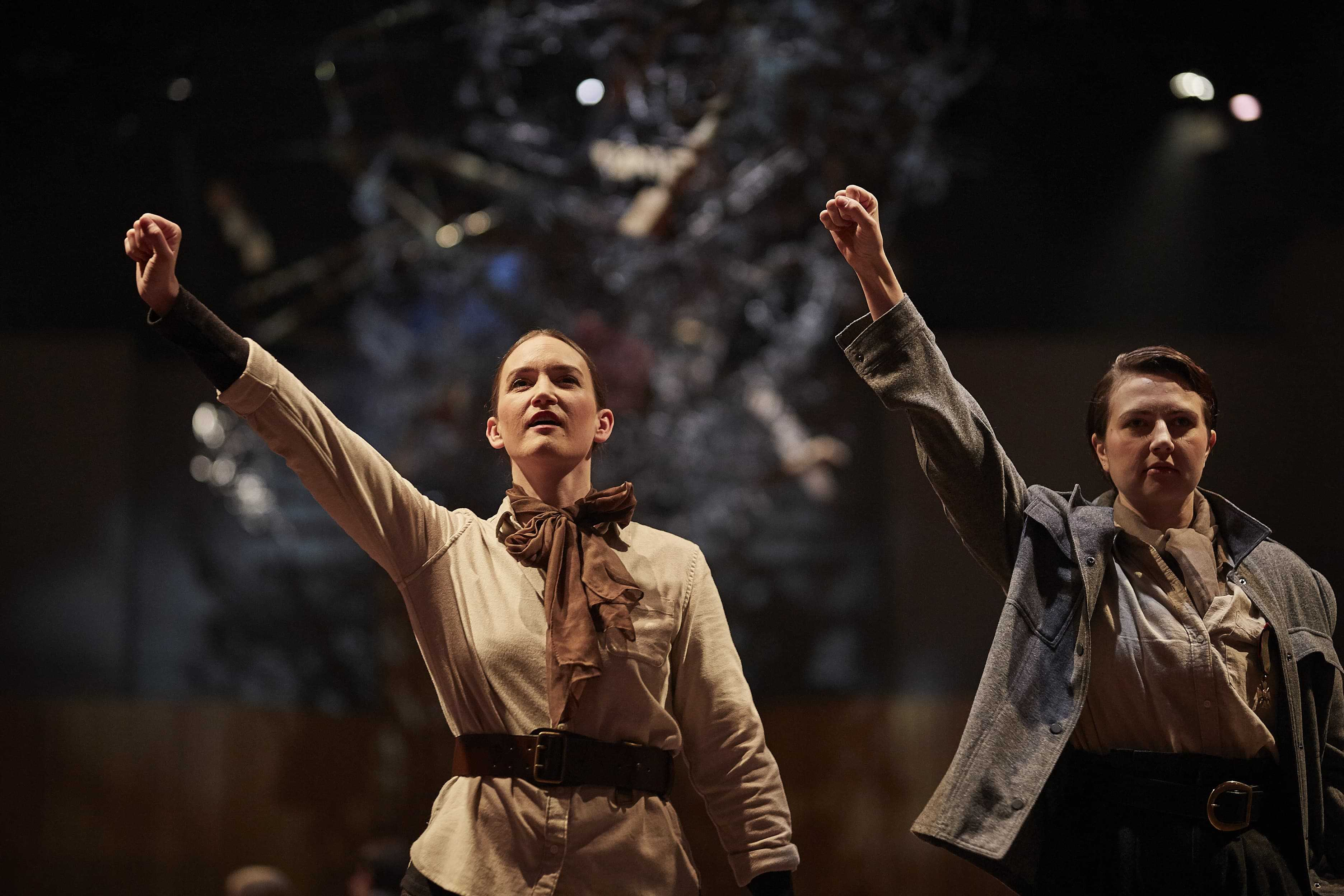 Two women on stage standing side by side with their right arms up punching the air