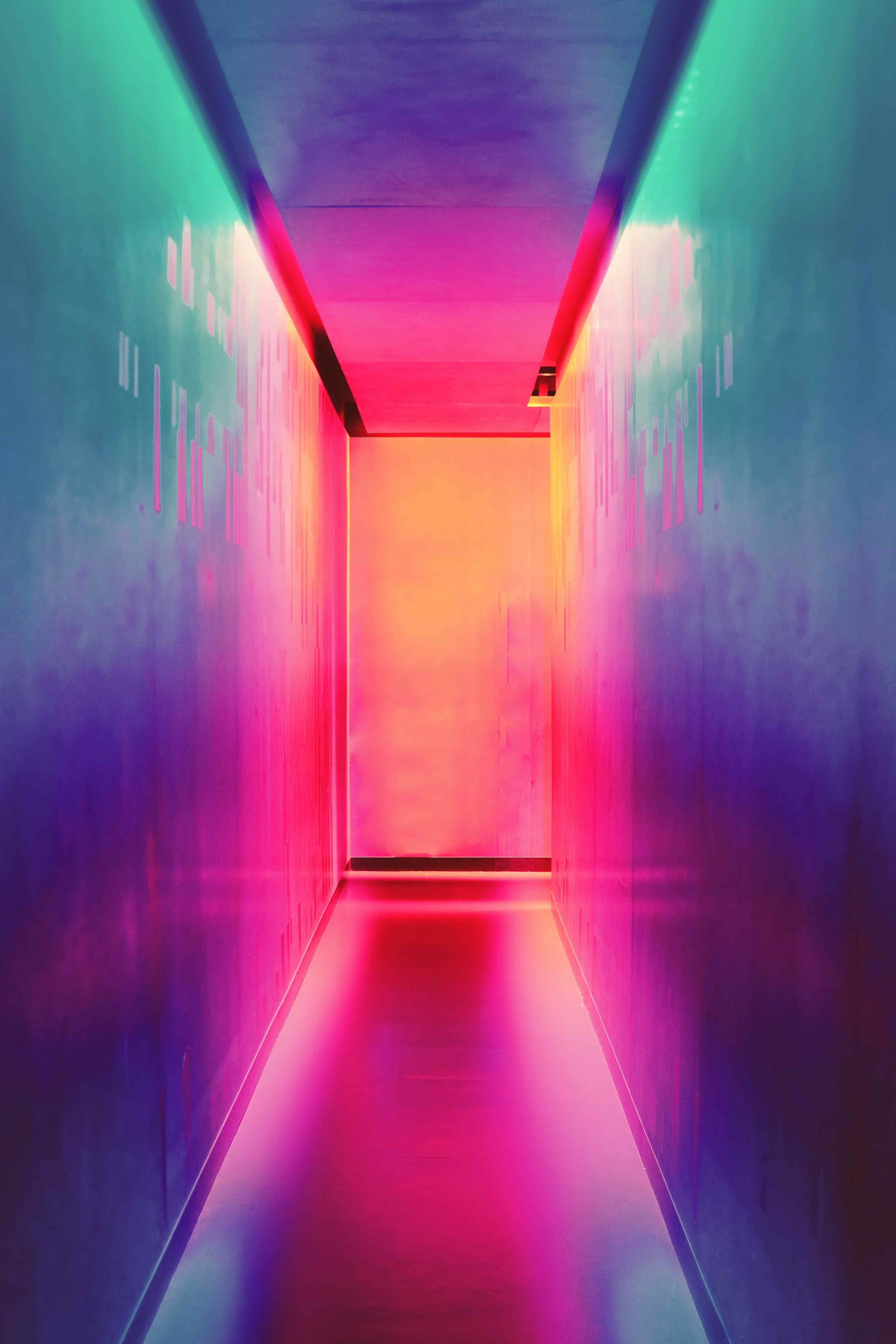 Neon pink and blue corridor leading to door