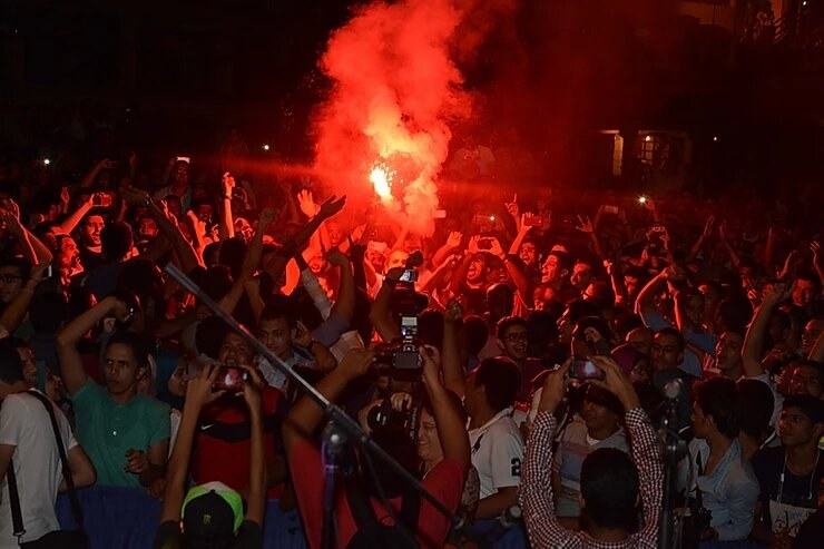 Image of large group of people in streets in Egypt with flare at night
